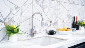 Wnętrze nowożytna kuchnia iluminuje z szarym kamiennym countertop z luksusowym washbasin obrazy stock