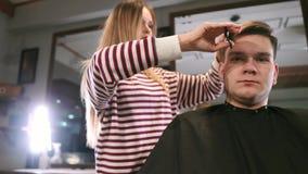 Wnętrze strzał pracować proces w nowożytnym zakładzie fryzjerskim Bocznego widoku portret dostaje modnego ostrzyżenie atrakcyjny  zbiory wideo