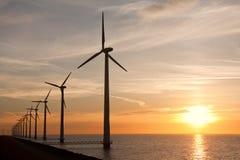 Wndturbines im Meer und in einem schönen Sonnenuntergang Stockfotografie