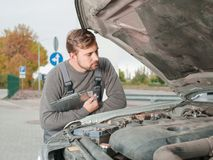 The white and young auto master diagnose the car outside. Stock Photos