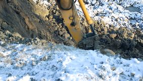 Wnter construction. Close-up of a bucket excavator raises the ground. Concept of construction. Close-up of a bucket excavator raises the ground. Concept of stock footage