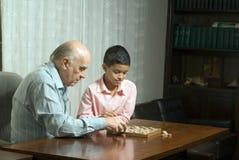 wnuczek dziadka grać siedzącego stół Zdjęcia Stock