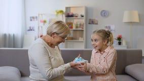 Wnuczka daje prezenta pudełku babcia i przytulenie, wakacyjna niespodzianka zdjęcie wideo