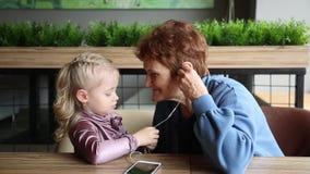 Wnuczka wkładał słuchawki w twój babci ucho zdjęcie wideo