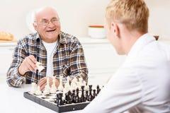 Wnuk i dziad bawić się szachy w kuchni Zdjęcie Stock