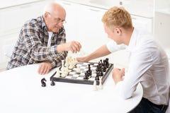 Wnuk i dziad bawić się szachy w kuchni Zdjęcie Royalty Free