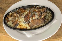 Wołowina jęzor z serem i pieczarkami Słuzyć w ceramicznym naczyniu Na drewnianym tle obraz royalty free