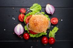 Wołowina hamburgery z warzywami Kłamstwa na czarnym textured tle z sałatą, pomidorami i pikantność, Odgórny widok zdjęcie stock