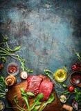 Wołowina stek i różnorodni składniki dla gotować na nieociosanym drewnianym tle, odgórny widok, rama obrazy royalty free
