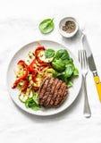 Wołowina stek z piec na grillu warzywami, słodkim pieprzem, zucchini i świeżymi szpinakami na lekkim tle, Wyśmienicie zdrowy fotografia stock