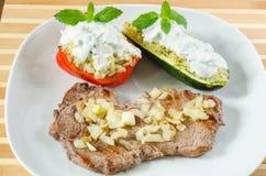 Wołowina stek z smażącymi cebulkowymi i faszerującymi warzywami Obrazy Stock