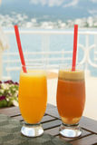 Wo玻璃用在桌上的汁液在海附近 免版税库存照片