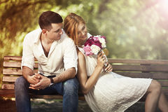坐在公园和人的年轻美好的夫妇提出wo 免版税库存图片