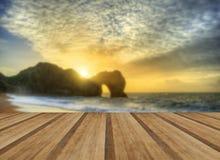 在海洋的充满活力的日出有在前景的岩石堆的与wo 免版税库存照片