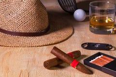 午睡-雪茄、草帽、苏格兰威士忌酒和高尔夫球司机在wo 免版税图库摄影