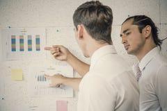 Wo-Arbeitskollegen besprechen sich mit dem Strategiediagramm Lizenzfreies Stockbild