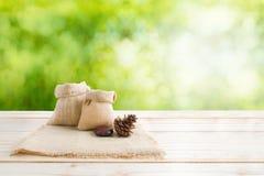 Wo of blank hemp sack bag and pine cones on wood table top floor Royalty Free Stock Image