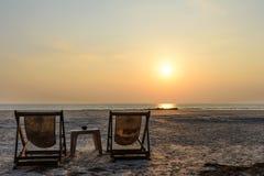 Wo-deckchair på stranden med solnedgångljus Royaltyfri Fotografi