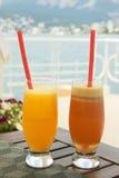 Wo-exponeringsglas med fruktsaft på tabellen nära havet Royaltyfri Foto