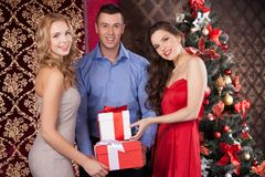 Wo happy women and man holding gift boxes. Stock Image