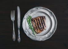 Wołowina stek z rozmarynami na rocznika metalu talerzu nad zmrokiem wo Zdjęcia Royalty Free