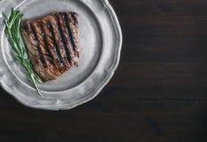 Wołowina stek z rozmarynami na rocznika metalu talerzu nad zmrokiem wo Zdjęcie Stock