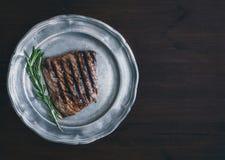Wołowina stek z rozmarynami na rocznika metalu talerzu nad zmrokiem wo Obraz Stock