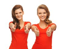 Wo teenage girls in red t-shirts showing thumbs up Stock Photo