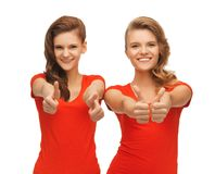 Wo teenage girls in red t-shirts showing thumbs up Stock Photos