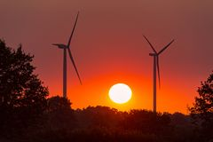 Wo wind turbines under a red sunset in summer. Wo wind turbines under a red sunset, in France during summer royalty free stock photo