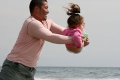 Woah!!!. Father playing with his daughter...pretending to throw her in the water stock images