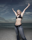 Woamn with arms outstretched. Attractive young woman with her arms outstretched posing on the beach Stock Photography