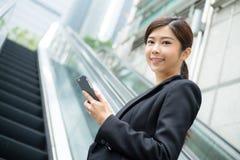 Woamn d'affaires tenant le téléphone portable et la position à l'escalator Images stock