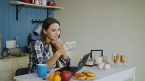 Woamn de sorriso alegre que fala o bate-papo video em linha usando o smartphone na cozinha em casa imagem de stock