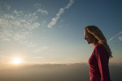 Woamn stands on a peak of mountain at sunset royalty free stock photo