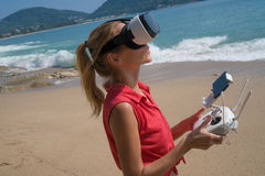 Woan with drone camera and virtual reality glasses taking photos and videos on the beach Royalty Free Stock Photography