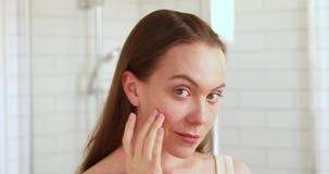 Woan wat betreft haar gezicht die van haar schone huid genieten stock videobeelden