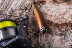 Wobbler y carrete del cebo de pesca con la línea en abedul Fotos de archivo libres de regalías