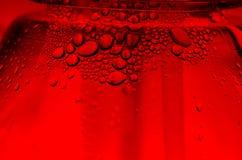 Wod krople na abstrakcjonistycznej czerwieni powierzchni. Zdjęcia Stock