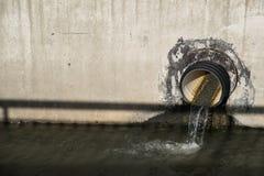 Woda drenuje przez drymby w kanał obraz stock