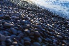 Woda i otoczaki błyszczymy przy wschód słońca w czarnym dennym Yalta quay seashore, Crimea obrazy stock