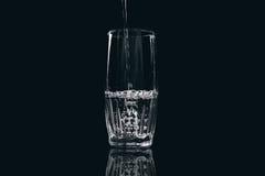 Woda nalewa w szkło na czarnym tle zdjęcia stock