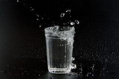 Woda nalewa w zlewkę na ciemnym tle Zdjęcie Stock