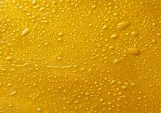 Woda opuszcza na żółtym tle, zakończenie up Zdjęcia Royalty Free