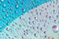 Woda opuszcza na dvd środkach, wod krople na kolorowym tle zdjęcia royalty free