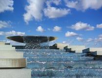 Woda płynie od pucharu spada kaskadą fontannę na tle niebieskie niebo Fotografia Stock