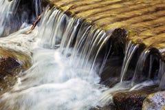 Woda płynie przez drewnianych bel, spada spada kaskadą puszek Zdjęcia Stock