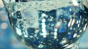 Woda płynie w szkło tworzy bąble i bryzga - zwolnione tempo zdjęcie wideo