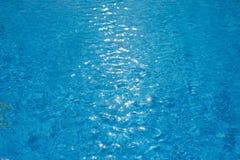 Woda pluskocze teksturę w pływackim basenie z pogodnym świeceniem Zdjęcie Royalty Free