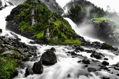 Woda siklawa płynie w zieloną dolinę na dwa innych sposobach Ziemia jest i skalista pełno kamienie a i zielona trawa Fotografia Stock
